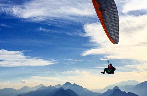 Gleitschirmflieger mit Gipfelpanorama