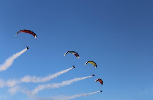 Vier Gleitschirmflieger beim Kunstflug mit Rauch