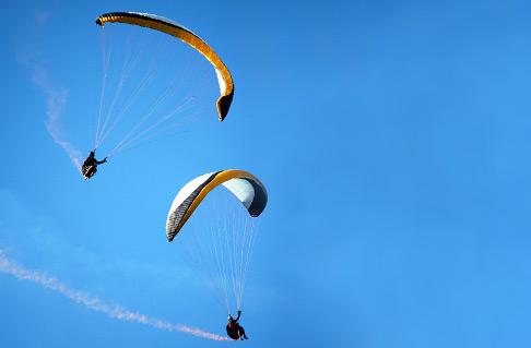 Zwei Gleitschirmflieger beim Kunstflug mit Rauch